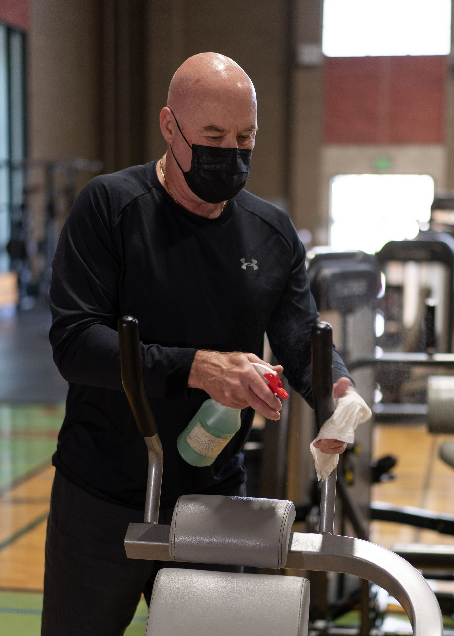 Man wearing a mask cleans the fitness equipment